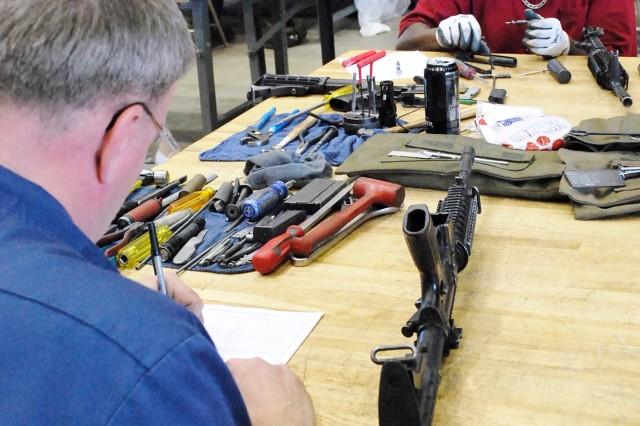 Contractors repair an M4 Carbine April 10, Fort Hood, Texas. (Photo by Jon Connor, ASC Public Affairs)