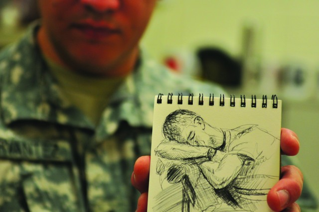 Master Sgt. Martin Cervantez, Musuem Support Center resident artist, displays the field sketchbook he carries while deployed, at the Museum Support Center at Fort Belvoir, Va.