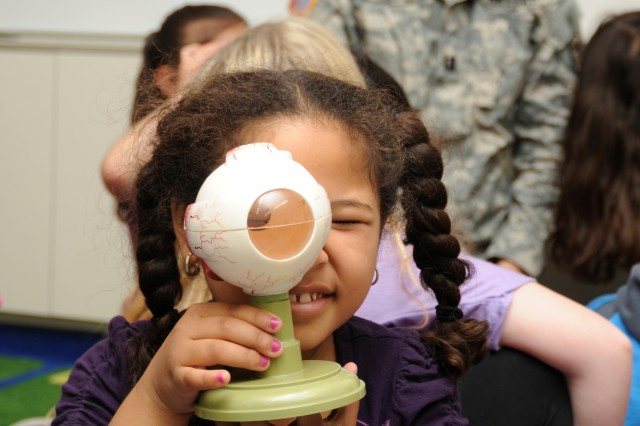 Sophia Dorsey, 7, a second-grader at Arnn Elementary School at Camp Zama, Japan, gets her turn to look through the magnified lens of a model eyeball as Capt. Lauren Parker, background, the optometrist assigned to Medical Department Activity-Japan, answers students' questions about her job.