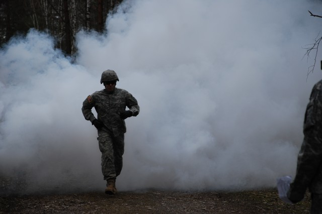 1st Lt. Lyndon Hill, assigned to 30th Medical Command, runs through a cloud of smoke at the obstacle course in Grafenwoehr during the Europe Regional Medical Command Best Junior Officer Competition April 17.