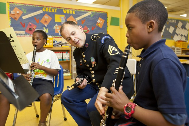 Sgt. 1st Class Michael Sears, clarinetist, works with Tony Davis, 3rd grade clarinetist, while Nikiya Monroe, 4th grade clarinetist, practices her music.  Soldier-Musicians from The United States Army Field Band joined OrchKids for a five-day workshop at Lockerman Bundy Elementary School.