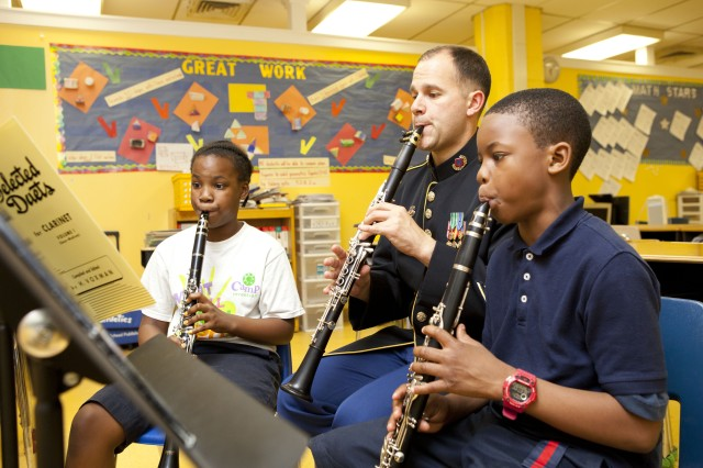 Sgt. 1st Class Michael Sears, clarinetist, plays along with Tony Davis, 3rd grade clarinetist, and Nikiya Monroe, 4th grade clarinetist, during a week-long workshop where members of The United States Army Field Band provided demonstrations and lessons to OrchKids in Baltimore.