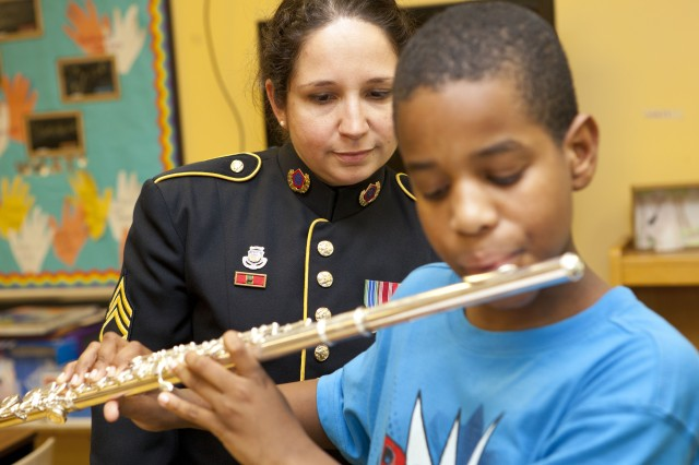 Staff Sgt. Katayoon Hodjati, flutist, instructs Jonah Laffiter, 5th grade flutist, during a week-long workshop in which Soldier-Musicians from The United States Army Field Band worked with OrchKids to promote positive social change through music.