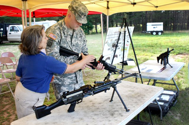 Kori Phillips, a U.S. Army Armament Research, Development and Engineering Center systems management engineer, talks to Sgt. Jason Reed about the chamber of the lighter version of the M249 machine gun at Picatinny Arsenal, N.J.