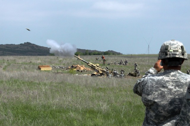 An advanced individual training Soldier from Fort Sill's 1st Battalion, 78th Field Artillery, watches as a round flies skyward from an M777 155mm howitzer manned by B Company, 1-321st Airborne Field Artillery, from Fort Bragg, N.C. The crew fired 16 rounds downrange in a coordinated fires exercise with rockets fired from HIMARS launchers for a time-on-target exercise that simultaneously landed artillery rounds and rockets on the same spot.