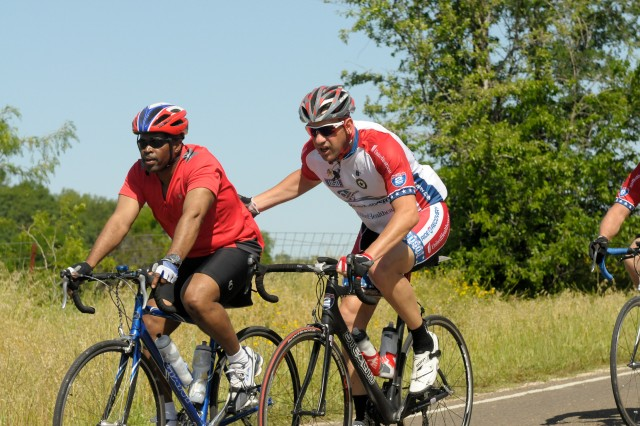 A cyclist motivates and pushes his comrade through a long stretch of road to the finish in Waco, Texas, during the Ride 2 Recovery Texas Challenge April 19, 2012. Ride 2 Recovery promotes mental and physical rehabilitation programs for wounded veterans that feature cycling as a core activity.