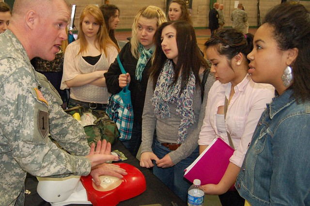 MILWAUKEE -- Sgt. John Whittenburg, Kenosha Recruiting Center, explains how combat medics use a chest seal in a tactical environment to Case High School students in Racine, Wis., during a Pathway to Success event April 19.