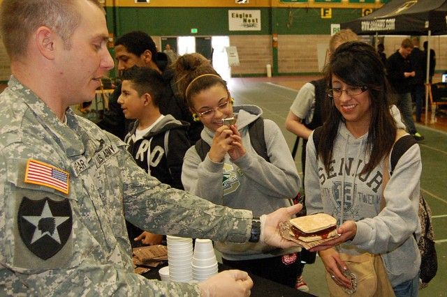 MILWAUKEE -- Staff Sgt. Paul Goodyear, Milwaukee Recruiting Center, uses components of a Meal, Ready-to-Eat to serve a field version of a vegetarian burger to Mariana Anguiano, a 12th grade student at Case High School, during a Pathway to Success event April 19.