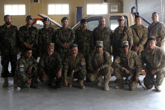 Members of the Afghan National Army, US Army and Royal Air Force, joined by their intepreter Wahed who works to bridge the language barrior, team up twice a week to maintain and service ANA vehicles and heavy machinery. SPC Farlane Breece, maintenance specialist for the US Army says this even is the highlight of his week. US Army photo by SPC Nicole Newton/Released