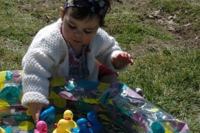 """Lorali Hudson, 11 months, daughter of Spc. Michael Hudson, from the 22d Chemical Battalion (Technical Escort), decides which duck to pick from the """"duck pond,"""" during the Defender's Spring Fling, held at McBride Field April 7.  The event, hosted by Company A 22d Chemical Battalion (Technical Escort), featured food, give-aways, and entertainment for all ages."""