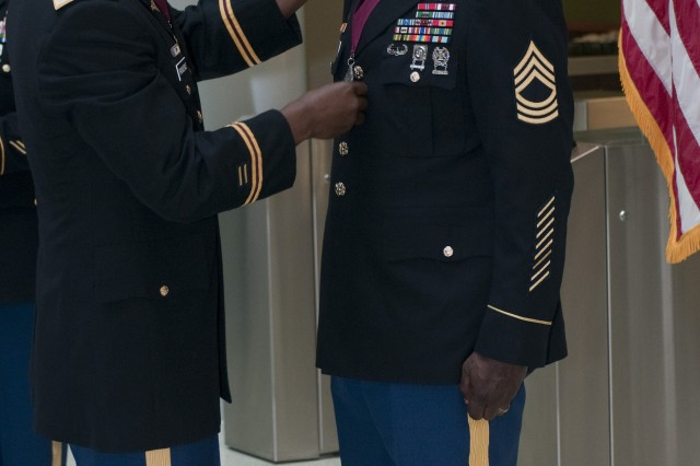 Col. Bertram Providence, Third Army/ARCENT surgeon, places the Order of Military Medical Merit Medallion on Master Sgt. Deon E. Dabrio, Third Army/ARCENT medical operations noncommissioned officer, during an induction ceremony at Third Army/ARCENT headquarters at Shaw Air Force Base, S.C. April 18.
