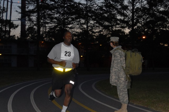 Pfc. Carly Schwartz, a medic with Headquarters, Headquarters Company 926th Engineer Brigade, observes contestants during the run portion of the Army Physical Fitness Test while Sgt. Frank Namukangula, 382nd MP Battalion rounds the third turn during the 412th Theater Engineer Command's 2012 Best Warrior Competition at Fort Rucker Ala., April 24, 2012. The best noncommissioned officer and junior enlisted Soldier from this competition will hold the title of Best Warrior for one year throughout the command and will compete in the United States Army Reserve Command's Best Warrior competition in June at Fort McCoy, Wis.  Winners of the USARC competition will compete at the Army level.