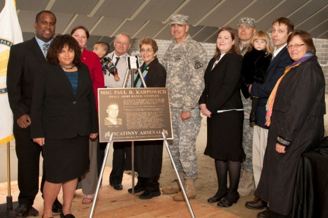 From left to right: Johnathan Holloway, Nataleigh Moore, Kristen Holloway, (being held) Paul Daniel Holloway, Richard and Claire Karpowich, Brig. Gen. Jonathan Maddux, Joanna Karpowich, Col. Scott C. Armstrong, (being held) Gabrielle Berna, Robert Berna, and Barbara Machak after participating in the unveiling of the Paul D Karpowich Small Arms Range Complex dedication plaque.