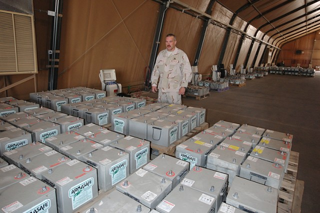 Michael Rogers, a turbine engine mechanic from Anniston Army Depot, Ala., serving as project lead on the Army Field Support Battalion-Kuwait, 402nd Army Field Support Brigade's Hawker Battery program at Camp Arifjan, Kuwait, looks over pallets of 12-volt batteries stacked for recharging, March 21, 2012. The re-charge and reuse or recycle stream has saved the Army more than $7 million between its inception in December 2010 and its conclusion in April 2012.