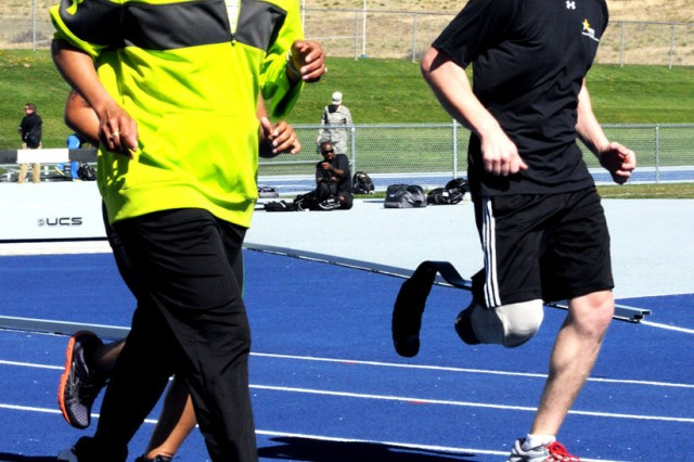 Retired Lt. Col. Sue Bozgoz, coach of the 2012 Warrior Games Army track athletes, runs alongside Spc. Brynden Keller, 82nd Airborne Division, and 1st Lt. Lacey Hamilton, 323rd Military Intelligence Battalion, during practice at the U.S. Air Force Academy, April 23, 2012. Fifty athletes from the Army and veteran wounded warrior community are representing the Army at the Warrior Games.