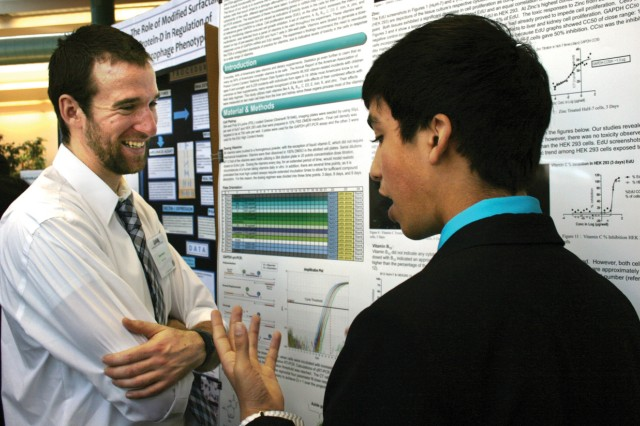 Devin Swanson, a moderator at the Rutgers symposium and an ARDEC engineer in the AMC Fellows Program, listens to a poster presenter on March 19.
