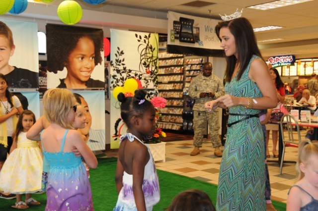 Katie Andrews, Miss Wiregrass Area, speaks with the children who modeled clothes in the fashion show before they sing a song together at the post exchange during the AAFES fashion show April 20.