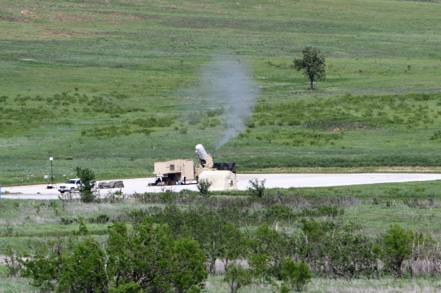 An enlarged image shows the C-RAM system as it blasts away at a simulated mortar during a cerifiction exercise April 19, at Thompson Hill Range.