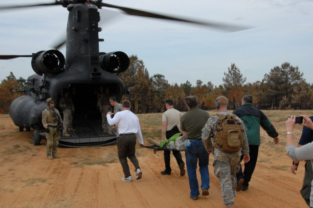 Joint Civilian Orientation Conference members carry a litter with a simulated casualty as they prepare to board a CH-40 Chinook Helicopter to leave the fictional country of Pinelandia at Fort Bragg, N.C., following a demonstration by members of the 75th Ranger Regiment. The JCOC provides an opportunity to gain a better understanding of the military, soldiers' service and the sacrifices their families make.