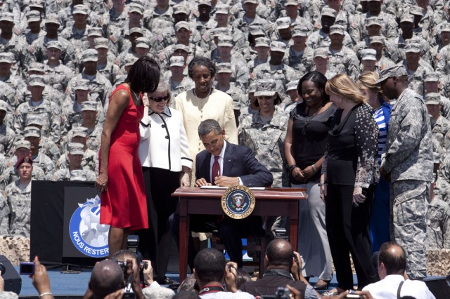 President Barack Obama signs an executive order preventing scams used to con veterans out of their federal education benefits, at Fort Stewart, Ga., April 27, 2012, as First Lady Michelle Obama and Fort Stewart Soldiers and civilians look on.