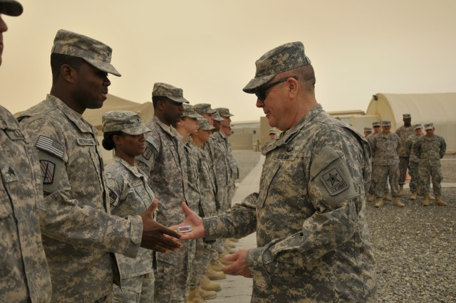 Lt. Gen. William Ingram, Jr., presents a National Guard coin of excellence to Sgt. Ferrell Reynolds of the North Carolina Army National Guard's 1452nd Transportation Company. The trip gave Ingram the opportunity to visit and talk with Guardsmen, and to see for himself the health and welfare of Army National Guard soldiers in Kuwait.