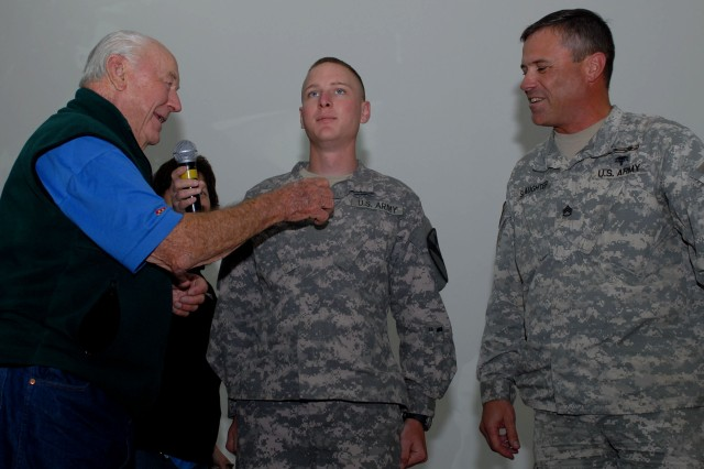 Heroic WWII fighter ace, jet pioneer and retired United States Air Force Maj. Gen. Chuck Yeager (left) pins private first class rank on Sean Stang in a promotion ceremony at Camp Buehring, Kuwait April 12. The ceremony took place during Yeager's vistit to Camp Buehring, and he performed the promotion at the request of Stang's platoon sergeant, Staff Sgt. Hank Slaughter (right). Stang, of Chandler, Ariz., and Slaughter, of Abilene, Texas, belong to Headquarters and Headquarters Troop, 1st of the 7th Cavalry, 1st Brigade Combat Team, 1st Cavalry Division, which is currently based at Camp Buehring.