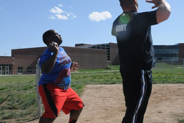 Army veteran Sean Hook (right) helps a Fort Carson, Colo., middle school student perfect his shot put throwing form during a training session April 26, 2012.  Hook began throwing discus and shot put six months ago and has already progressed to the level where he was selected to represent the Army at the 2012 Warrior Games from April 30 to May 05, 2012.