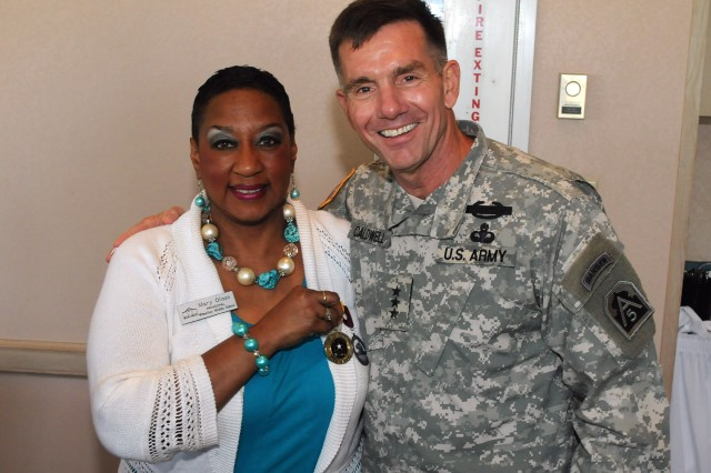 FORT SAM HOUSTON, Texas - Lt. Gen. William Caldwell, commanding general, U.S. Army North, and senior commander, Fort Sam Houston and Camp Bullis, presents a Fort Sam Houston Fiesta Medal to Mary Olison, principal, Wheatley Middle School, during an Adopt-a-School luncheon at the Fort Sam Houston Golf Club. Units from Fort Sam Houston have partnered with nine nearby schools to provide mentors and tutors for area school children and to participate in activities with the schools. (U.S. Army photo by Staff Sgt. Keith Anderson, Army North PAO)