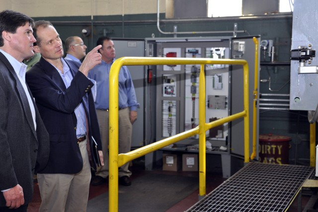 Dr. Jim Galvin, pointing, who is the OSD ESTCP Water Program Manager, asks Ken Swanson, the Director of Engineering for Fireye's Combustion and Controls Group, how the various aspects of the prototype continuously monitored the concentrations of oxygen and carbon dioxide.