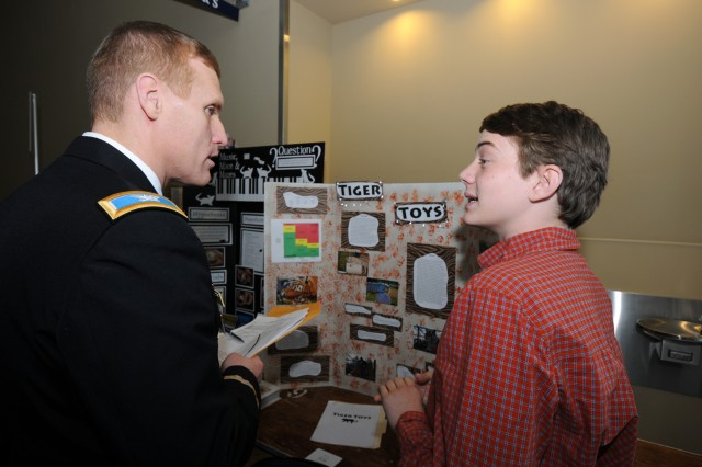 Col. Stephen C. Gomillion, Commander of the National Ground Intelligence Center, left, talks with Daniel Neale, 14, Buford Middle School about his science project, Tiger Toys.  Photo by Nathan Lee, NGIC Photographer.
