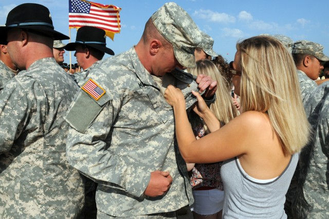 "FORT HOOD, Texas -- Pfc. Cody Muir, from 2nd Squadron ""Sabre"", 3rd Cavalry Regiment, is pinned with the Expert Infantryman Badge by his wife, Laura, at Veterans Field Apr. 27. Muir earned the badge for a successful completion of the EIB course. (U.S. Army photo by Sgt. Lance Pounds)"