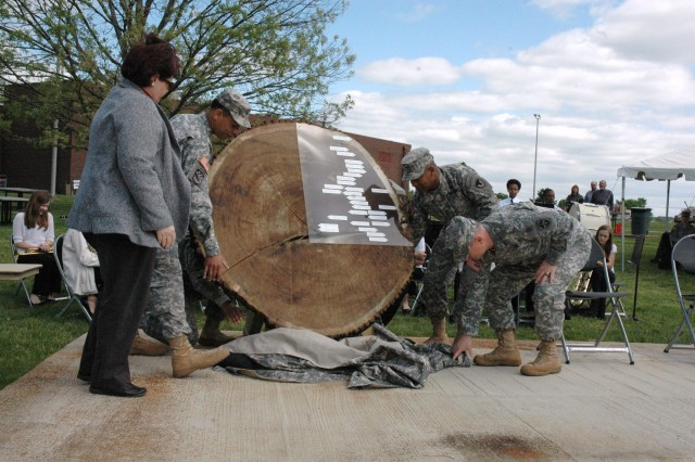 """From left) Director of the APG Museum, Gail Fuller, APG Garrison Commander Col. Orlando Ortiz, APG and CECOM Commander, Maj. Gen. Robert Ferrell, and ATEC-AEC Brig. Gen. John Regan unveil a tree slice known as a """"biscuit,"""" taken from a black oak tree that stood on APG since the early 1800s during APG's Earth Day/ Arbor Day celebration April 27. The tree oak biscuit will be displayed in the APG Museum for educational purposes."""