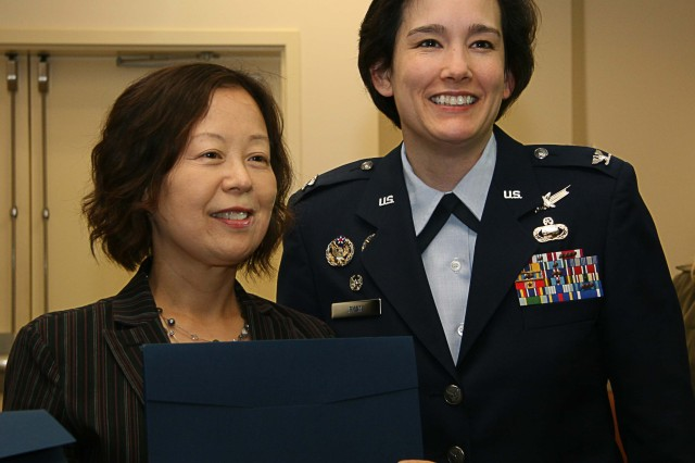PRESIDIO OF MONTEREY, Calif. - DLIFLC Assistant Commandant Col. Laura Ryan congratulates newly sworn-in U.S. citizen and DLIFLC faculty member Sohee Koo April 3, 2012.
