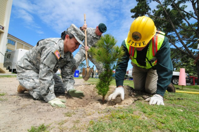 PRESIDIO OF MONTEREY, Calif. - (from left to right) Presidio Garrison leadership Command Sgt. Maj. Olga Martinez and Col. Joel J. Clark plant a tree with assistance from City of Monterey arborist Steve Morton.