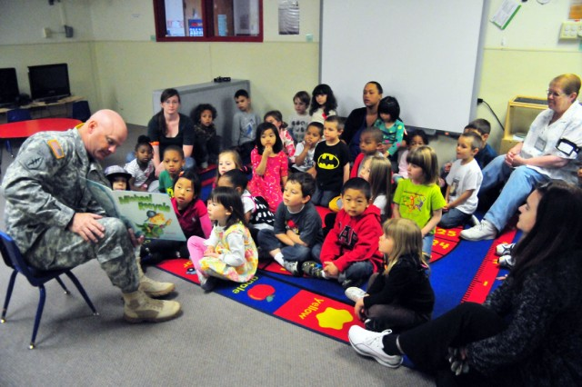 """PRESIDIO OF MONTEREY, Calif. - Preschoolers listen to Presidio of Monterey Garrison Commander Col. Joel J. Clark read the book """"Michael Recycle"""" about recycling as part of the Earth Day celebration at the Monterey Road Child Development Center on April 23."""