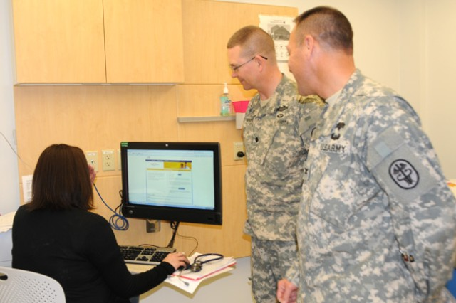 Col. Patrick N. Denman and Lt. Col. Andrew A. Powell explain the benefits of having a nurse and touch-screen computer in the exam room with a patient.