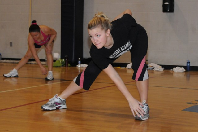 Courtney Vigil, military spouse, does crossover stretching during an exercise class. People participating in the Beach Body Bingo program can mark their Bingo card for any exercise classes they attend at either of the fitness facilities on Fort Rucker.