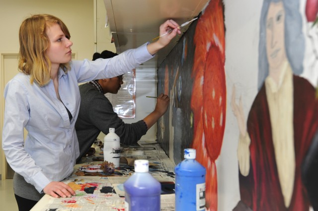 Trisha Dring, a senior at Zama American High School at Camp Zama, Japan, paints a mural on the wall of her school's physics classroom, a project she and five of her classmates conceived as part of an end-of-year presentation. Also pictured is freshman Nathan Fuentes, a partner in the project.