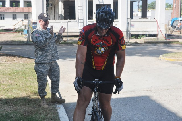 FORT BENNING, Ga. -- Lt. Col. Dan Hodne, commander, U.S. Army Marksmanship Unit, greets Jeremy Staat as he peddles his bike to the USAMU unit headquarters.  Staat and Wesley Barrientos, two Iraqi combat veterans, are riding their bikes from California to Washington D.C. to raise awareness for our nation's veterans.  (Photo by Michael Molinaro, USAMU PAO)