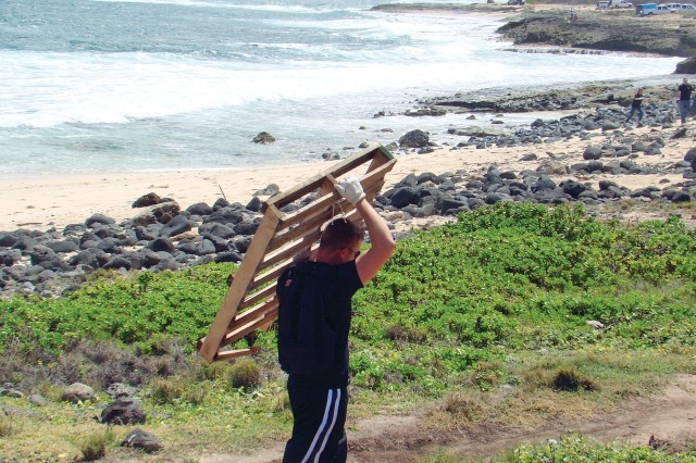 Spc. Erick Olson, with 225th BSB, 2nd BCT, 25th Inf. Div., picks up a wooden palette near the shore at Kaena Point State Park, Saturday.