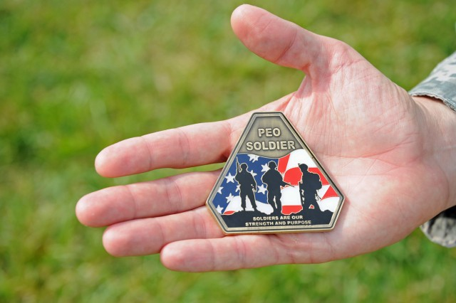 "The face of the new PEO Soldier coin which was created by Maj. Joel Dillon. It features the silhouettes of three Soldiers against an American flag with the inscription, ""Soldiers Are Our Strength and Purpose."""
