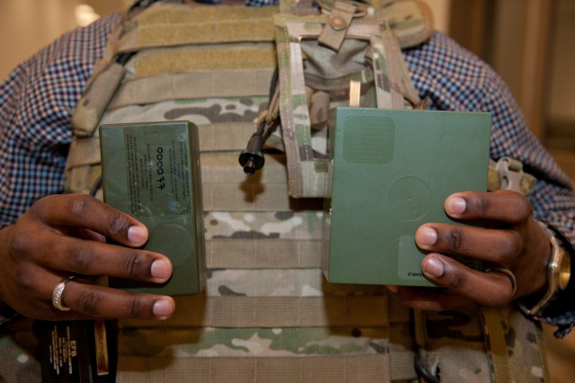 Christopher Hurley, an electronics engineer with the U.S. Army Research, Development and Engineering Command, holds a Half-Size BA-5590 Battery, left, compared with the standard version.