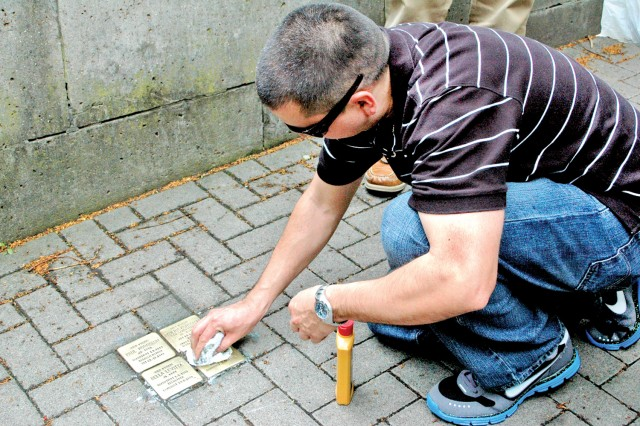 Air Force Master Sgt. David Medrano, a government ground representative with the Defense Contract Management Agency Southern Europe Aviation Program Team, cleans Holocaust memorial stones in Wiesbaden, Germany.