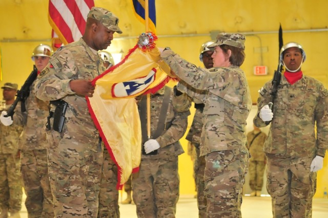 """Brig. Gen. Kristin K. French, the commanding general of the 3d Sustainment Command (Expeditionary), and Command Sgt. Maj. Karl A. Roberts Sr., the 3d ESC's senior enlisted leader, uncase the command's colors during a transfer of authority at Kandahar Air Field, Afghanistan May 7. During the ceremony, the 3d ESC took command of Joint Sustainment Command """" Afghanistan from the 4th ESC and became the senior logisticians in county and are responsible for all logistics operations within the Afghanistan theater. (U.S. Army photo by Sgt. Andrew Valles)"""
