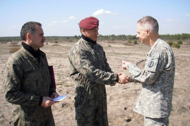 Polish army officers Lt. Col. Jan Ekiert (left), brigade executive officer, 6th Airborne Brigade, and Col. Tomasz Piekarski (center), brigade deputy commander, present the Polish army Parachute Badge to Lt. Col. Jerzy Zubr (right), U.S Army Training and Doctrine Command Liaison Officer at Pustynia Bledowska drop zone, April 20.