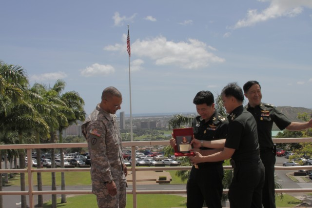 HONOLULU -- Lt. Gen. Surasak Karnjanarat, Royal Thai Army, presents a gift to Col. J. Anson Smith, chief of staff, Pacific Regional Medical Command and Tripler Army Medical Center, during a tour, here, May 7, 2012. Smith also presented Karnjanarat with a koa wood carving of Tripler.   Karnjanarat, along with Maj. Gen. Chatchalerm Chalermsukh and Capt. Jiraporn Theeradejpong of the Royal Thai Army went on a tour of the hospital to include the Sleep Center, Pain Management Clinic and Emergency Room before heading to Camp Smith to meet with members of Pacific Command.