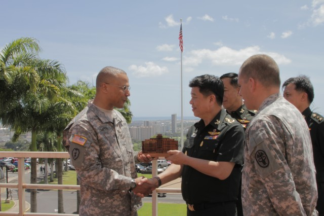 HONOLULU -- Col. J. Anson Smith, chief of staff, Pacific Regional Medical Command and Tripler Army Medical Center, presents Lt. Gen. Surasak Karnjanarat, Royal Thai Army, with a koa wood carving of Tripler, during a tour, here, May 7, 2012.  Karnjanarat, along with Maj. Gen. Chatchalerm Chalermsukh and Capt. Jiraporn Theeradejpong of the Royal Thai Army went on a tour of the hospital to include the Sleep Center, Pain Management Clinic and Emergency Room before heading to Camp Smith to meet with members of Pacific Command.