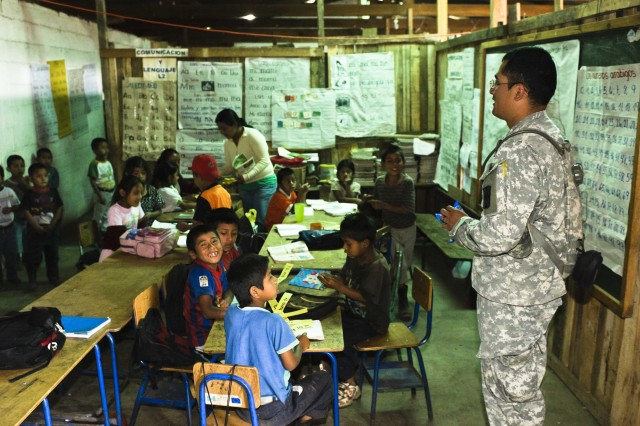 Sgt. 1st Class Angel Lopez, 142nd Military Intelligence Battalion, 300th MI Brigade, Utah National Guard, deployed in support of Beyond the Horizon Guatemala 2012, distributes candy to children in class in Sarrax-Och, Guatemala.  While the military engineers that he is supporting with his linguistic abilities work on these children's new school complex, Lopez visited them in their temporary facilities.