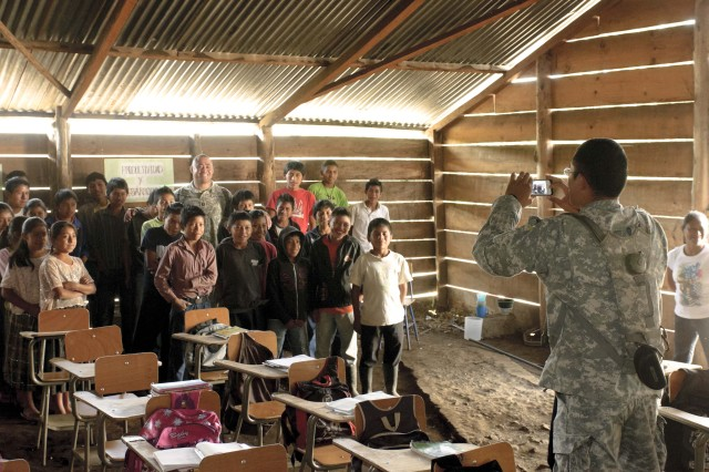While touring the temporary school facilities in Sarrax-Och, Sgt. 1st Class Angel Lopez, right, of the 142nd Military Intelligence Battalion, 300th MI Brigade, Utah National Guard, deployed in support of Beyond the Horizon Guatemala 2012, takes a picture of a fellow Soldier with the students in Sarrax-Och, Guatemala.  Lopez volunteered linguistic support to the engineers building the residents of Sarrax-Och a new school complex.