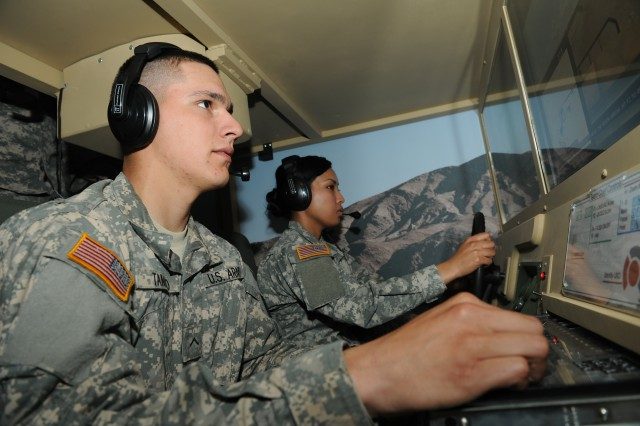 Pvt. Armando Tamayo, left, and Spc. Veasna Mean, both 509th Route Clearance Company, 5th Engineer Battalion, hone their IED identification skills in a driving simulator in the MCIT.